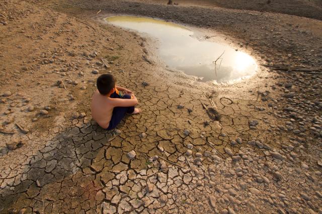 Een Aziatische jongen zit bij een kleine plas water op uitgedroogde grond, Shutterstock