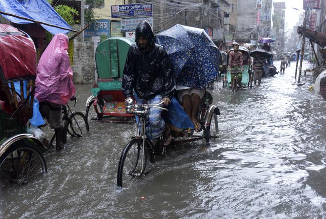 Een man fietst door de overstroomde straten van Bangladesh.